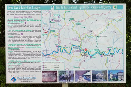 parc naturel: SAINT-CIRQ-LAPOPIE - JULY 20, 2014: Tourist information sign post located in Saint-Cirq-displaying a map and additional infomation of Parc naturel regional des Causses du Quercy in France.