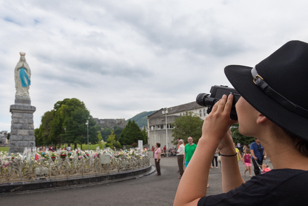 prominent: LOURDES - JULY 23, 2014: A tourist is filming La Vierge Couronnee or Statue of the Crowned Virgin with a Rhonda CAM. This prominent statue is a familiar landmark and a traditional meeting point. Editorial