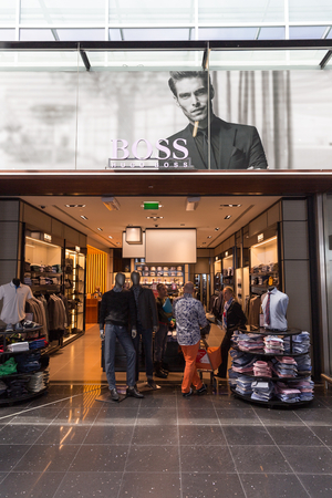 hugo: AMSTERDAM - 19 JULY, 2014: Travellers shopping at Hugo Boss in Schiphol Airport.