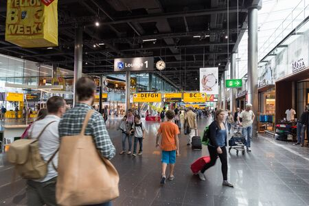 schiphol: AMSTERDAM - 19 JULY, 2014: Travellers shopping in Schiphol Airport.