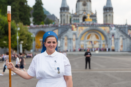 devout: LOURDES, FRANCE - JULY 23, 2014: A religious sister is standing on Rosary square in front of The Basilica of the Immaculate Conception.