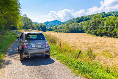 backroad: CAVAZET, FRANCE - JULY 24, 2014: Fiat 500 (Type 312) parked in the French country side at Cavazet in the Midi Pyrenees. The Fiat 500 hatchback is a city car built by Italian automaker Fiat since 2007.