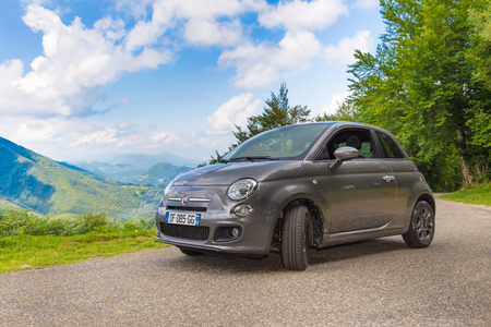 backroad: RIMONT, FRANCE - JULY 24, 2014: Fiat 500 (Type 312) parked in the French country side at Rimont in the Midi Pyrenees. The Fiat 500 hatchback is a city car built by Italian automaker Fiat since 2007.