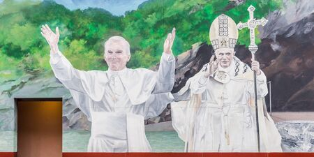 LOURDES, FRANCE - JULY 23, 2014: Mural of the late Pope John Paul II and Benedict XVI in Lourdes, one of the most popular Catholic pilgrimage sites in the world.