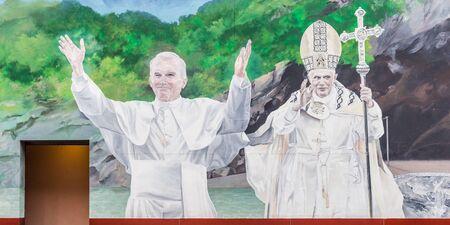 sotana: LOURDES, FRANCIA - 23 de julio 2014: Mural del difunto Papa Juan Pablo II y Benedicto XVI en Lourdes, uno de los lugares de peregrinaci�n cat�licos m�s populares del mundo. Editorial