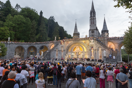 torchlight: LOURDES - JULY 23, 2014: Pilgrims partaking in La Procession Mariale Aux Flambeaux or the Torchlight Marian Procession in Lourdes. The torchlight procession takes place at the Domain daily at 9.00pm.