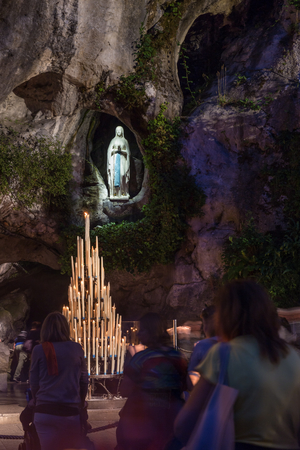 devout: LOURDES, FRANCE - JULY 23, 2014: Pilgrims visiting the cave at Massabielle at night to say prayers.