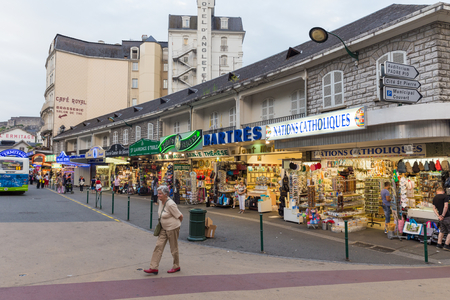 conceived: LOURDES, FRANCE - JULY 23, 2014: Typical souvenir shop as found in Lourdes, France. Most of the shopping opportunities in Lourdes are especially conceived for pilgrims.