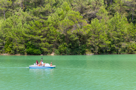 mediaeval: CARCASSONNE, FRANCE - JULY 26, 2014: Family peddling on a hydrocycle on Lac de la Cavayère. The lake is an artificial lake close to the mediaeval town of Carcassonne.
