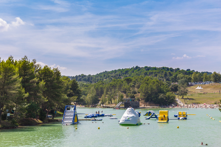 mediaeval: CARCASSONNE, FRANCE - JULY 26, 2014: Inflatable water playground at Lac de la Cavayere. The lake is an artificial lake close to the mediaeval town of Carcassonne.