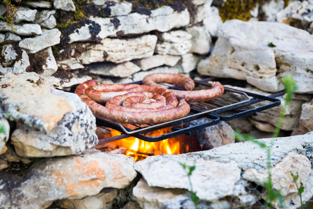outdoor fireplace: Fresh beef sausage grilling on a self built natural stone barbeque