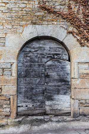 view of a wooden doorway: Old rustic wooden door in a stone structure