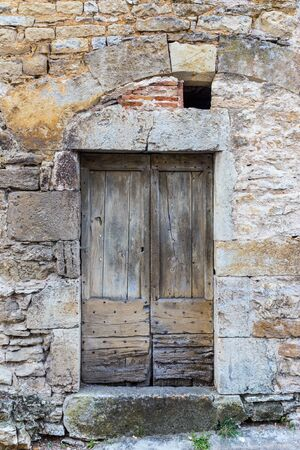 view of a wooden doorway: Old worn wooden door in a stone structure