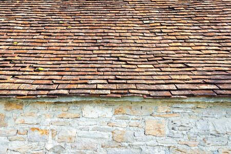 red clay: Part of red clay tiled roof and natural stone wall Stock Photo