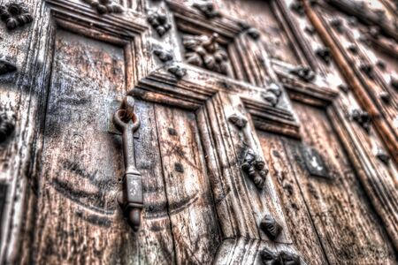 relievo: Metal door knocker on a heavy relief door with decorations Stock Photo
