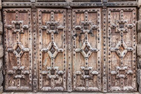 view of a wooden doorway: Heavy wooden doors with relief carved patterns