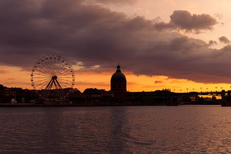 Toulouse ferris wheel on the Garonne rive bank at dusk Stock Photo