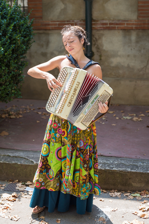 playing the market: TOULOUSE, FRANCE - JULY 27, 2014: A female street musician is playing the accordion at the March� Saint Aubin, the Saint Aubin Market, in Toulouse. Marche Saint Aubin is only held on Sundays.