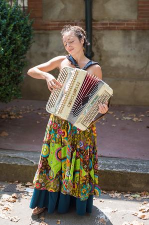 acordeón: TOULOUSE, FRANCIA - 27 de julio 2014: Un músico callejero femenino está jugando el acordeón en la Marcha Saint Aubin, el Mercado de Saint Aubin, en Toulouse. Marche Saint Aubin sólo se lleva a cabo los domingos.