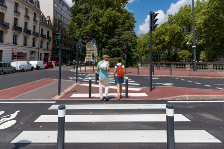 distinguishing: TOULOUSE, FRANCE - JULY 27, 2014: 2 locals crossing a zebra crossing. French government is trying to improve matters but French drivers still pay little attention to pedestrians and zebra crossings. Editorial
