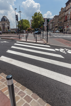 distinguishing: TOULOUSE, FRANCE - JULY 27, 2014: Zebra crossing in Toulouse France. French government is trying to improve matters but French drivers still pay little attention to pedestrians and zebra crossings.