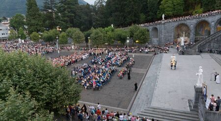 devout: LOURDES, FRANCE - JULY 23, 2014: Overall view of the mass held in the evening on Rosary Square at the Basilica in Lourdes. 5,000,000 pilgrims and tourists visit Lourdes every season. Editorial