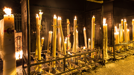 devout: LOURDES - JULY 23, 2014: Specially crafted candles burning in Lourdes. One of the great traditions of Lourdes is to light a candle in front of the Grotto.