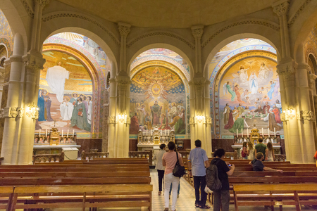 pentecost: LOURDES, FRANCE - JULY 23, 2014: Tourists visiting the side chapel mosaic depicting the Pentecost inside the Rosary Basilica in Lourdes.