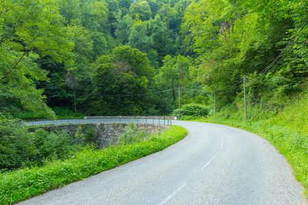 backroad: Sharply curved dowhhill winding road in the Pyrenees in Boussenac in France Stock Photo