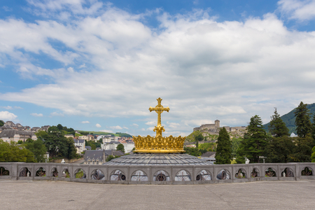 devout: The Upper Basilica with gilded crown ad cross in Lourdes Stock Photo