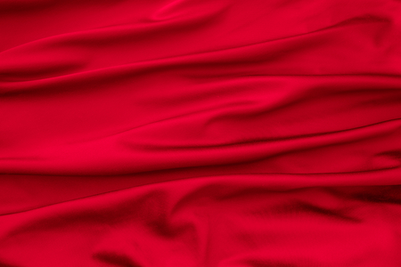 Soft velvet piece of red fabric with folds to be used as background photo