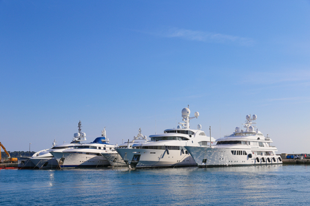 synonymous: CANNES, FRANCE - APRIL 12, 2015: Yachts anchored in Port Pierre Canto at the Boulevard de la Croisette in Cannes, France.  Cannes is synonymous with glamour thanks to its world-famous film festival.