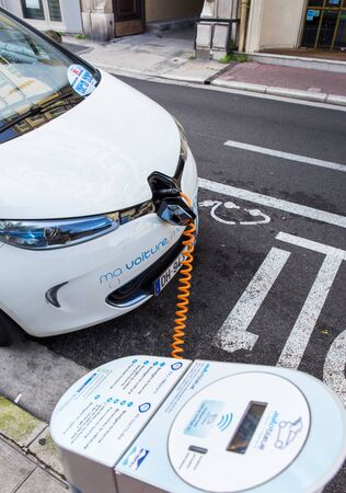 electric station: NICE, FRANCE – APRIL 11, 2015: A Renault Zoe electric car is connected to a Auto Bleue charging station. Renault Zoe is a five-door supermini electric car produced by the French manufacturer Renault. Editorial