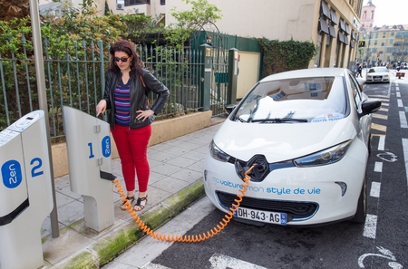 france station: NICE, FRANCE – APRIL 11, 2015: A woman is programming the Auto Bleue charging station to electrically charge a Renault Zoe electric car in Nice, France.