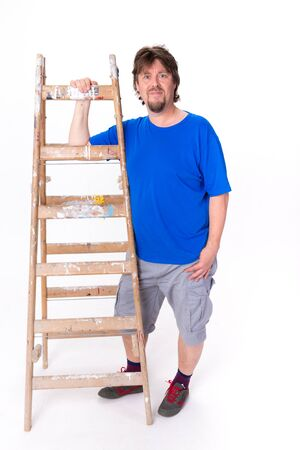 Smiling man standing next to a ladder isolated on a white background photo