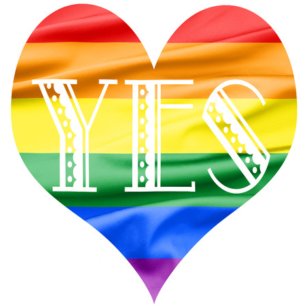 lesbian love: Soft Velvet Piece of Fabric heart shape in rainbow color with the word YES written Stock Photo