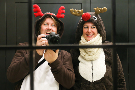 Young couple dressed up as two reindeer at Christmas in Madrid taking a selfie in an hotel mirror photo