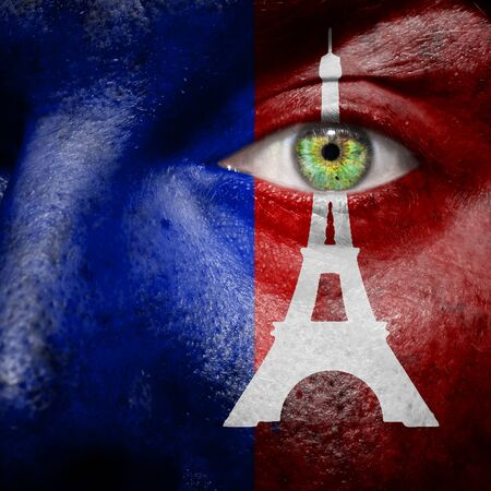 Paris flag with Eiffel tower painted on a mans face to support the people of Paris photo