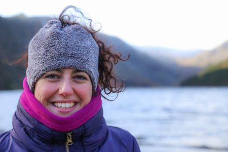 Portrait of a happy smiling beautiful woman wearing colorful warm winter clothes with a red face from the cold standing in mountain landscape in Ireland