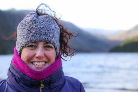 Portret van een gelukkig lachend mooie vrouw, gekleed in kleurrijke warme winterkleren met een rood gezicht van de kou staan in berglandschap in Ierland
