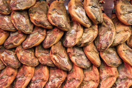 jamones: Un montón de jamones que cuelgan de ganchos en un supermercado en España Foto de archivo