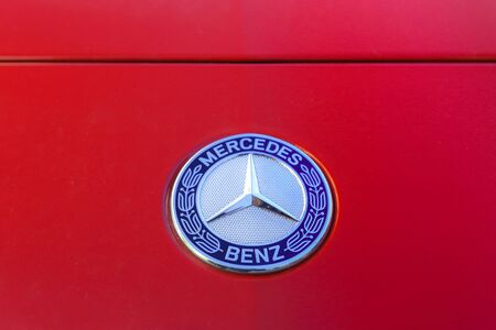 unique characteristics: MADRID - DECEMBER 30, 2014: Red Mercedes-Benz hood with recognisable three pointed star round logo
