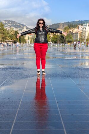 soleil: Happy smiling woman standing in the middle of the Fontaine du Soleil on Place Massena in Nice France