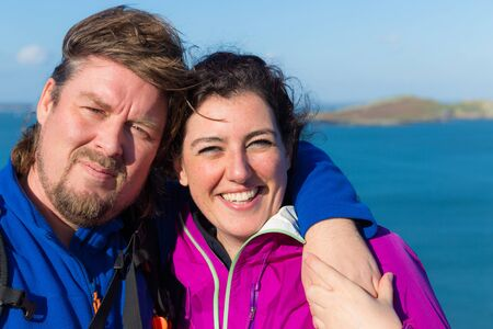 Young trendy smiling and hugging couple in Ireland wearing outdoor gear with the Irish sea in the background photo