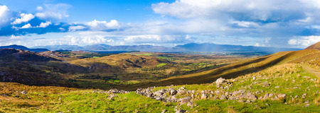co  kerry: Panorama of a colourful undulating Irish landscape in Kerry with rocks in the foreground and rain and rainbow in the distance