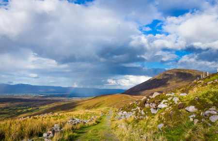 co kerry: Raining down and sunshine with rainbow on the countryside in Kerry in Ireland