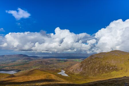 co kerry: Valleys and mountains in County Kerry on a summer day with deep blue sky and white clouds in Ireland Stock Photo