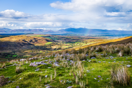 irish landscape: Colourful undulating Irish landscape in Kerry with grass in the foreground and rain and rainbow in the distance