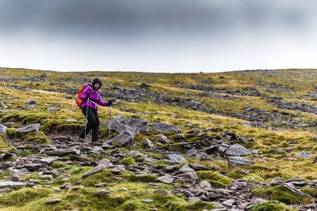 femal: Femal hiker hiking downhill from a mountain crossing a rocky hillside