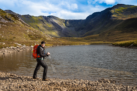 Female hiker with trekking poles and backpack posing lake side with the Macgillycuddys Reeks  mountain range in the background